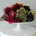 Cake plate filled with hydrangeas, succulents, cymbidiums and dahlias.