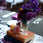 Centerpiece of lilac, sweetpeas and dahlias gathered in a cut crystal vase, adorned with peaches, grapes and books.