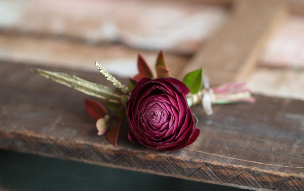 Designed by Amanda of Alluring Blooms, Wisconsin.  Burgundy ranunculus Sprig of red huck Sprig of gold grivellia Wire/tape Pure silk ribbon $13.00