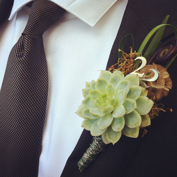 Lily grass, fiddle head fern, moss, and scabiosa pod, and a succulent, The Number 22 was added for the groom it was his late fathers number. wrapped with silver bullion wire.. I charged 28.00