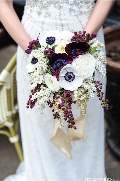 Cascading plum & white bouquet of anemones, ranunculus and andromeda