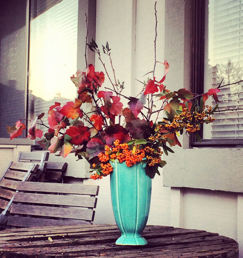 turquiose vase with orange fall flowers