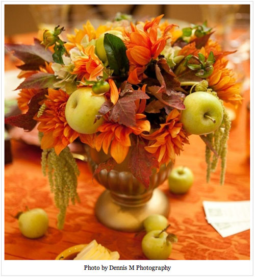 orange fall flower arrangement with green apples