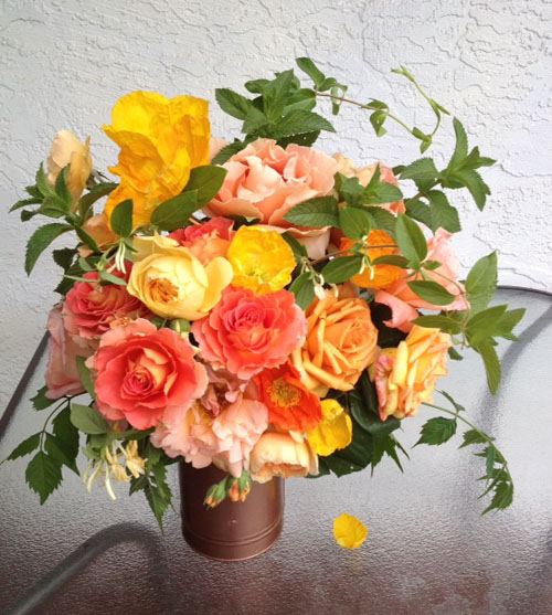 orange and yellow garden roses with mint in copper vase