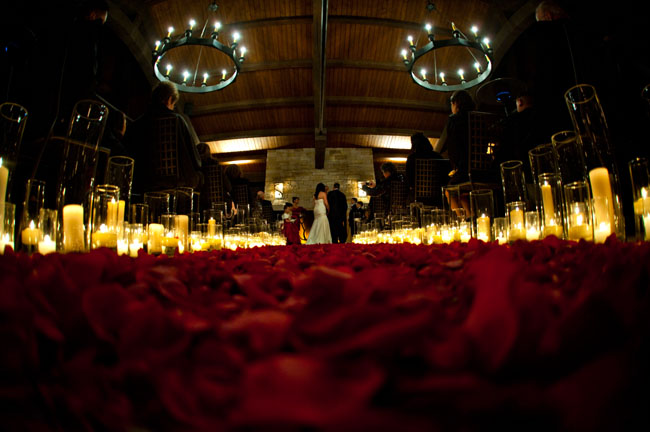 Red rose petal and candle lined ceremony aisle by The Flower House