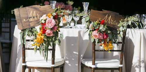 Fleurie, Bride and Groom chair decorations with flowers