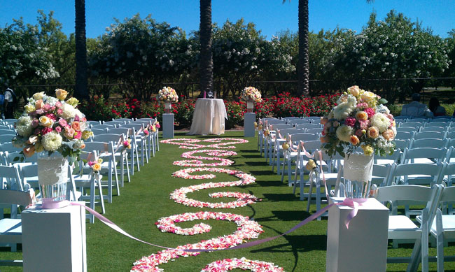 Designed by Fleurie of Reedley California, Wedding Ceremony aisle with petals placed in scrolls pattern.