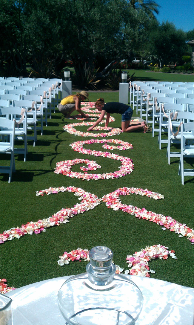 Designed by Fleurie Flowers, setting up the wedding ceremony aisle with rose petal scrolls