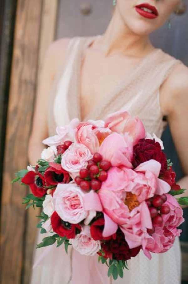 Emily Burton Bridal bouquet of coral charm peonies red hypericum red anemones pink roses