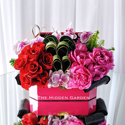 Hidden Garden, Pink box filled with pink and red roses with heart shapped flax leaves