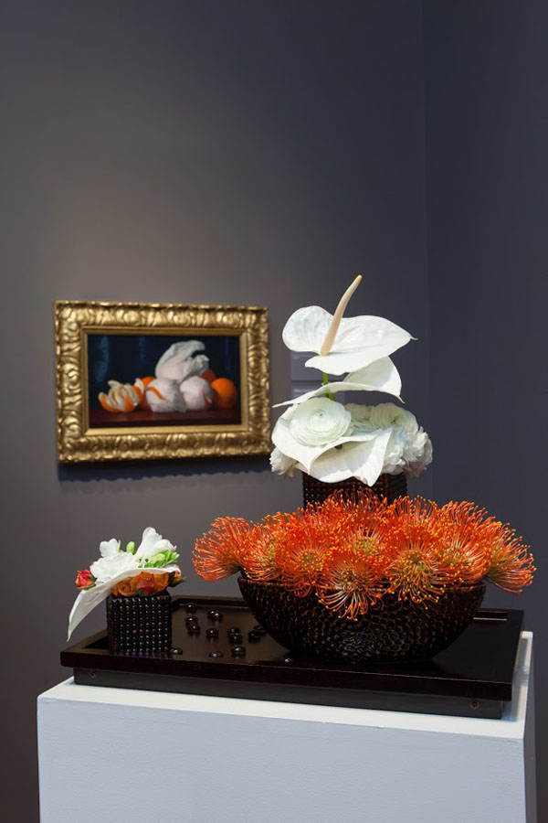 San Francisco Bouquets To Art, William Joseph McCloskey, Oranges in Tissue Paper, c. 1890. Oil on canvas. Fine Arts Museums of San Francisco, gift of Mr. and Mrs. John D. Rockefeller, III.  Floral design by Friends of Fioli. Photograph © Greg A. Lato / latoga photography