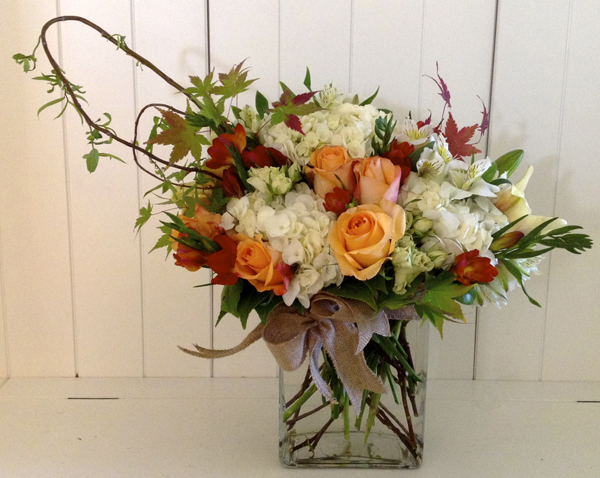 Green Bouquet Floral Design; flower arrangement of white hydrangea, orange roses, maple leaves, red freesia