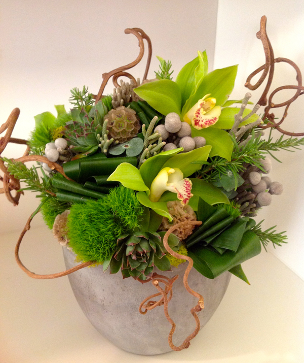 Green Bouquet Floral Design; flower centerpiece of green cymbidium orchids, grey berzillia berries, green trick dianthus, succulents, scabiosa pods and kiwi vine