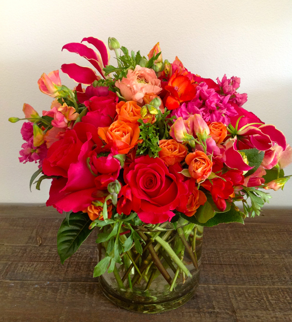 Green Bouquet Floral Design; red roses, gloriosa lilies, red freesia, magenta pink stock flowers, mambo orange spray roses