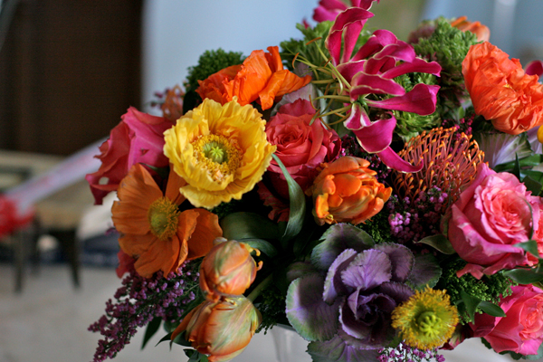 White Magnolia, arrangement of orange and yellow poppies, orange tulips, purple kale, gloriosa lilies, roses, lilac