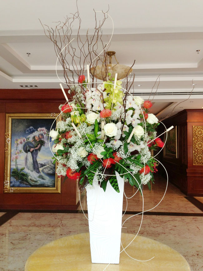 38 Degree Flowers Co., Hotel Lobby in Vietnam, Large floral display of cymbidium orchids, orange pincushion proteas, white roses and baby's breath