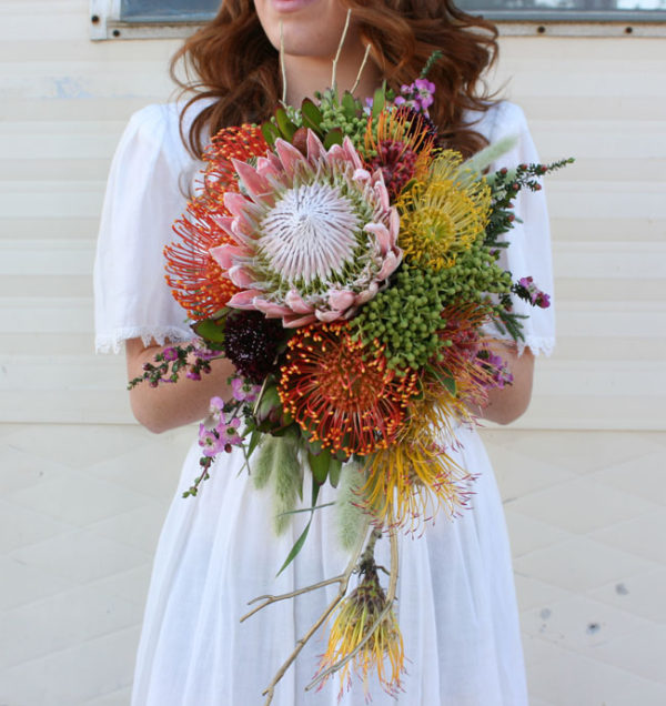 Fleurie Florals of Reedley, California, Cascading bridal bouquet of pincushion proteas, berzillia berries