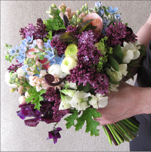 Floral Verde, Bridal bouquet of purple sweet peas, blue tweedia, scented geranium, lilac, white ranunculus, peach stock, white sweet peas, fern fronds