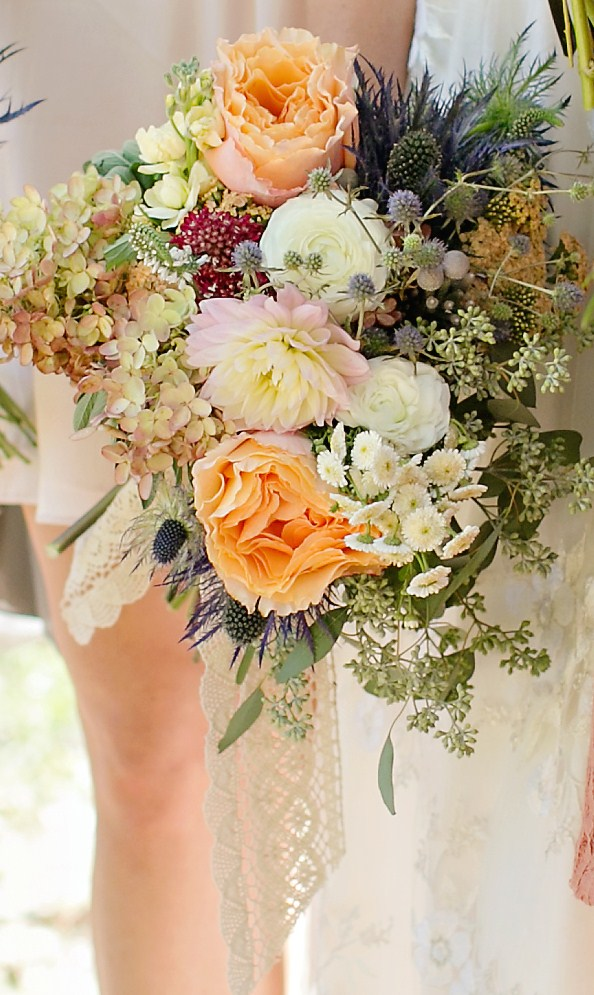 Gertie Mae's Bridal Bouquet of peach garden roses, hydrangeas, blue thistle, dahlias, ranunculus, seeded eucalyptus, veronica