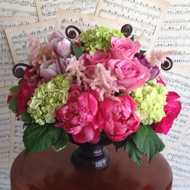 Designed by Luv Peace Flowers, centerpiece of coral charm peonies, pink astilbe, green hydrangeas, fern fronds, tulips