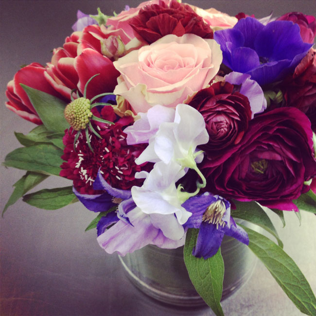 Cymbidium Flower Shop, New Hampshire - Centerpiece of burgundy ranunculus, purple sweet peas and clematis, tulips