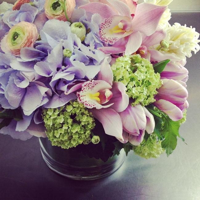 Cymbidium Flower Shop, New Hampshire - flower centerpiece of purple hydrangea, pink cymbidium orchids, pink tulips and ranunculus with viburnum