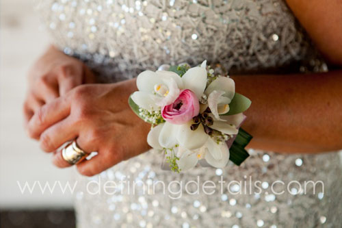 KRISanthemums Corsage - White cymbidium orchid, pink ranunculus, eucalyptus, bear grass, bracelet and one bling pin $45.00