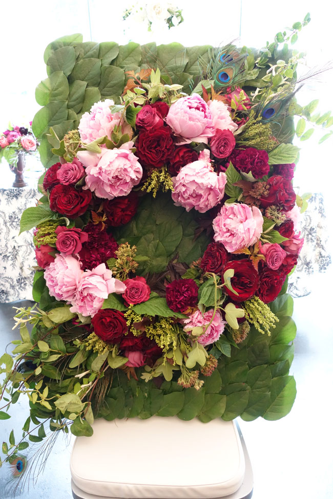 Pink wreath of peonies and roses on salal board for escort card table display