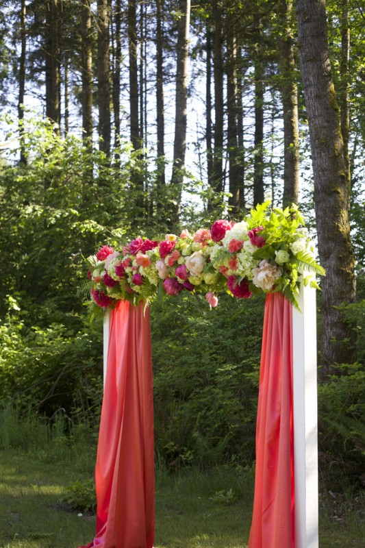 Modern Floral Arch with coral fabric, green, coral and peach flowers for the Flirty Fleurs Floral Design Class in Washington.