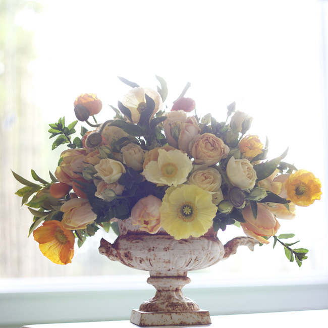 Bella Fiori, yellow floral arrangement of poppies and roses in a compote urn