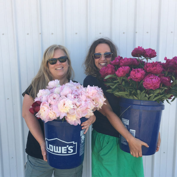 Alicia Schwede and Robyn Rissman holding buckets of Peonies for the Field to Vase Dinner
