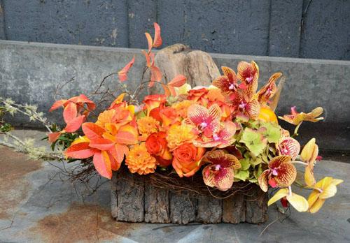 orange dahlias and orchids flower centerpiece