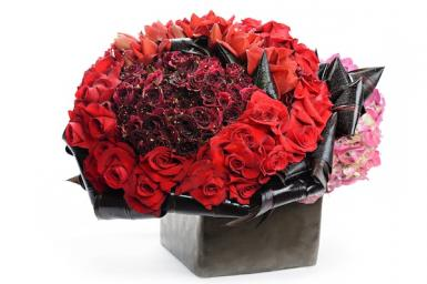 Tic Tock Florals, dark red roses and red roses with a collar of black ti leaves