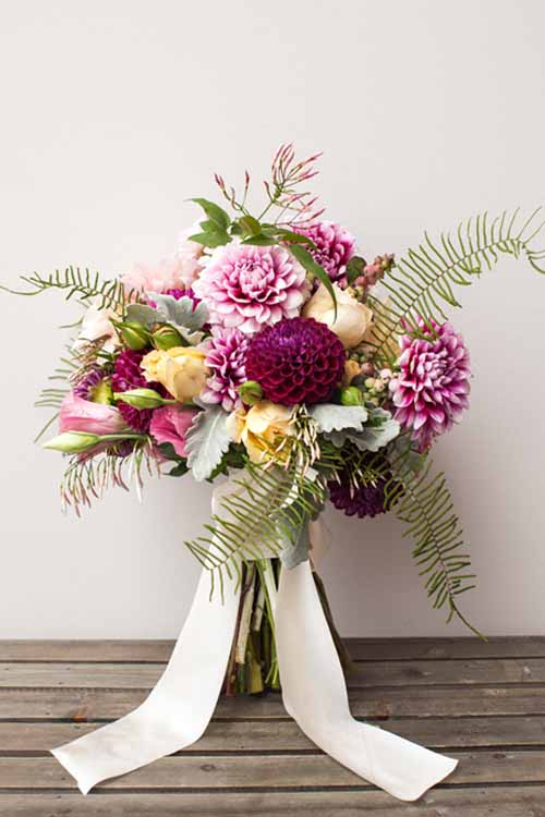 Floral Design & Styling Violet and Verde, Bridal bouquet of sea star fern, burgundy dahlias, yellow garden roses, pink lisianthus