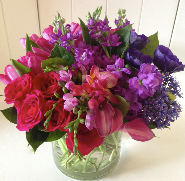 Green Bouquet Floral Design; flower centerpiece of magenta pink roses, pink calla lilies, pink freesia, lavender stock flowers, purple anemones,