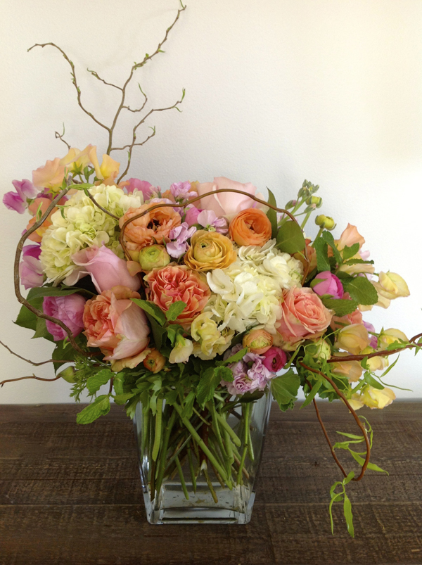 Green Bouquet Floral Design; flower arrangement  of white hydrangea, peach roses, peach ranunculus, pink roses, pink stock flowers, mint, peach sweet peas