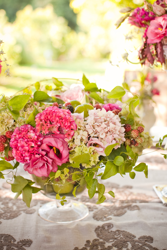 Flirty Fleurs, centerpiece with persimmons, pink and green hydrangeas, pink coxcomb, clematis vines