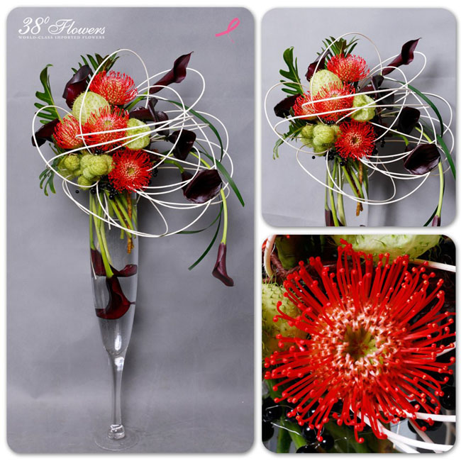 38 Degree Flowers Co., Contemporary floral design with plum callas, orange pincushions and lily grass