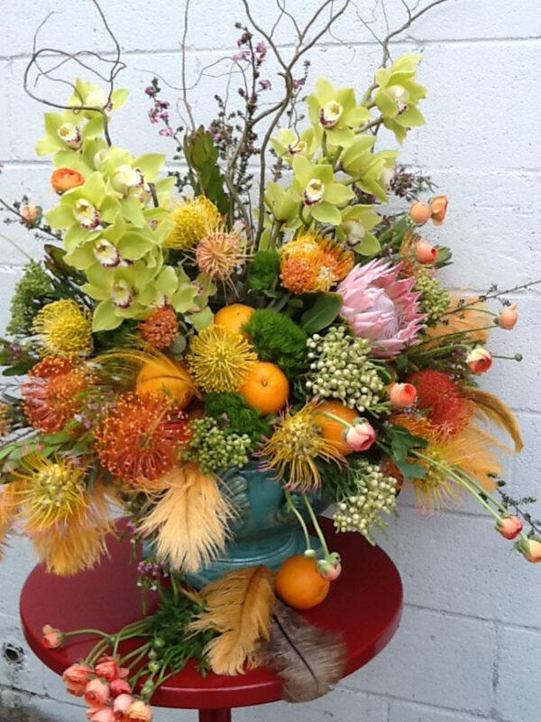 Mt Lebanon Floral Design, flower arrangement with oranges, feathers, cymbidium orchids, proteas