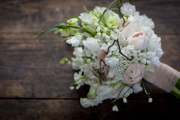 Jay Archer Floral Design, Bridal bouquet with white muscari, sweet peas, lily of the valley, pink ranunculus, hellebores wrapped with pink ribbon