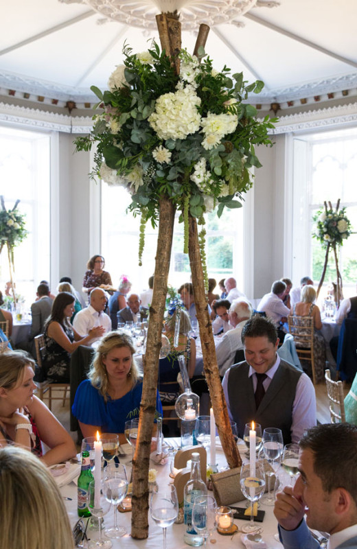 Jay Archer Floral Design, Centerpiece made with birch poles which hold an elevated floral arrangement of green and white flowers