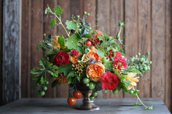 Floret Flower Farm - bronze compote flower arrangement of orange peach garden roses, tomatoes, cranberry viburnum, red ranunculus, nasturtium