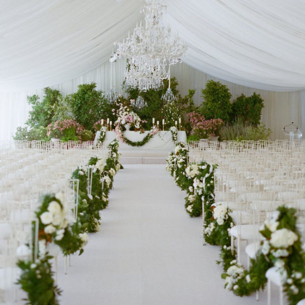 Lewis Miller Design, Ornate ceremony decor with a background of plants, aisle lined with draping garlands